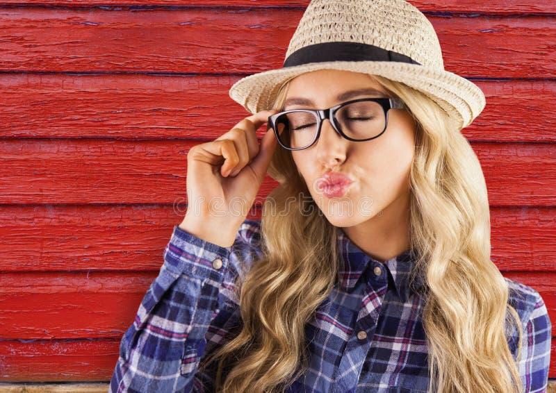 mulher do moderno com os vidros que enviam um beijo com fundo de madeira vermelho fotografia de stock