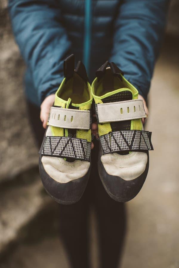 Mulher do montanhista com suas sapatas de escalada colocadas em suas mãos fotos de stock royalty free