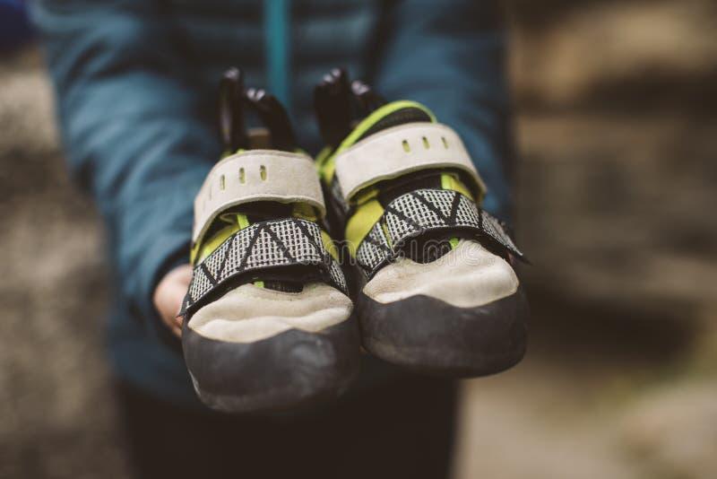 Mulher do montanhista com suas sapatas de escalada colocadas em suas mãos fotografia de stock