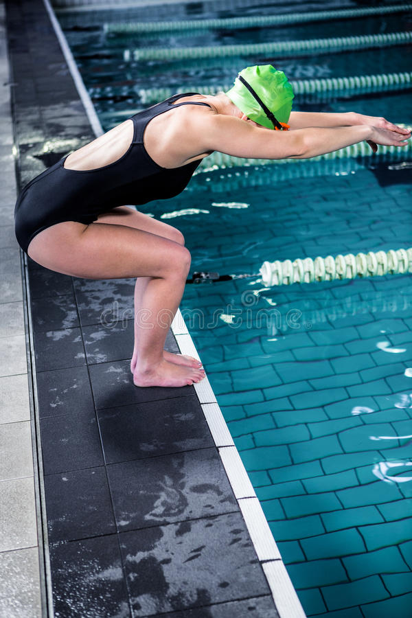 Mulher do nadador aproximadamente a mergulhar na piscina imagem de stock