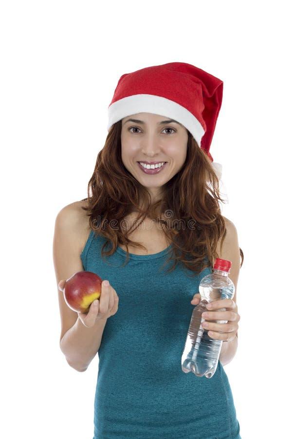 Mulher do Natal com uma maçã e uma água fotografia de stock
