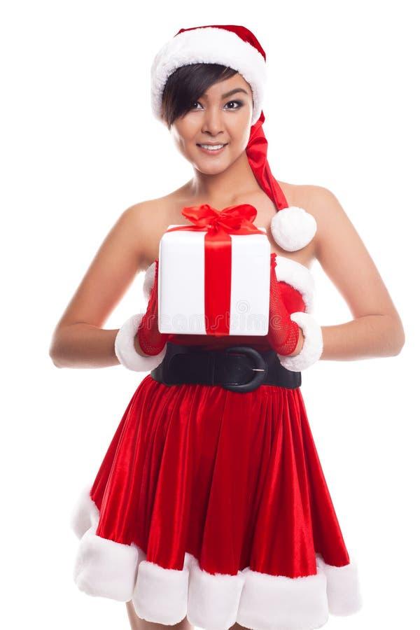 Mulher do Natal do chapéu de Santa que mantém o sorriso dos presentes do Natal feliz foto de stock royalty free