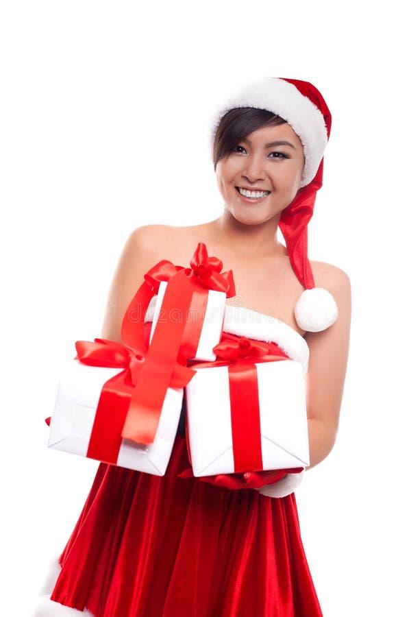 Mulher do Natal do chapéu de Santa que mantém o sorriso dos presentes do Natal feliz fotos de stock royalty free