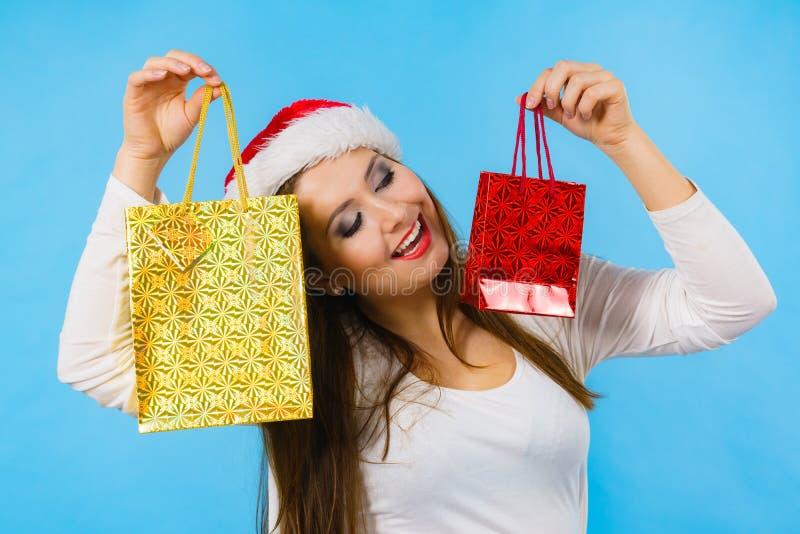 A mulher do Natal feliz guarda presentes ensaca foto de stock