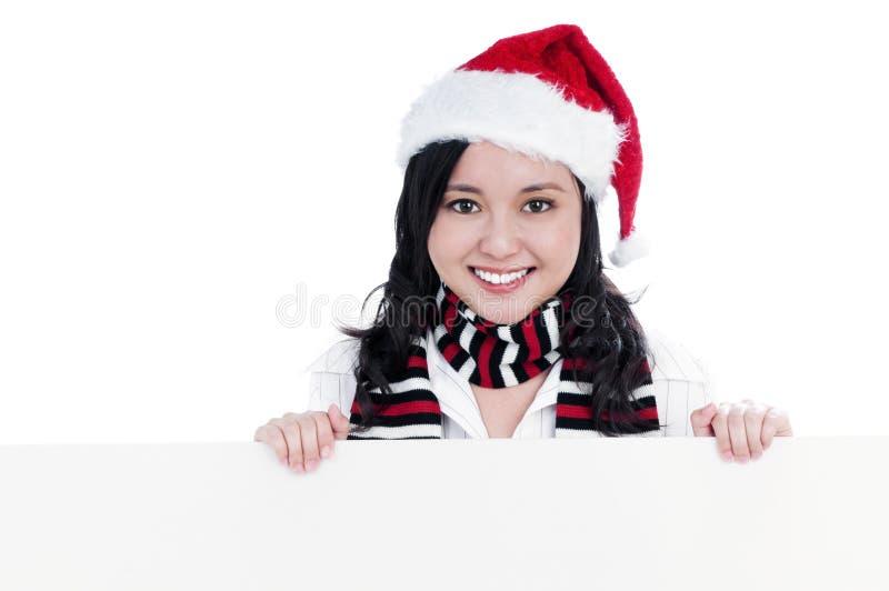 Mulher do Natal feliz que prende o quadro de avisos em branco imagem de stock royalty free
