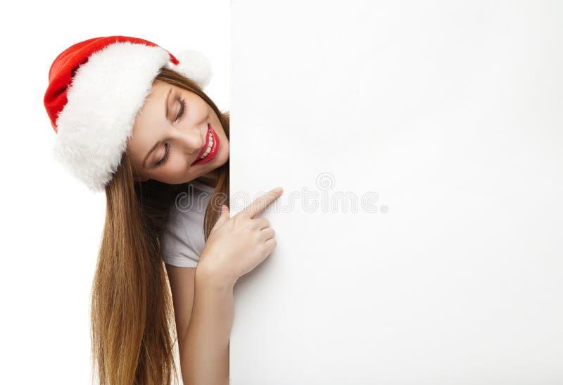 Mulher do Natal no chapéu de Santa que aponta a placa vazia fotos de stock