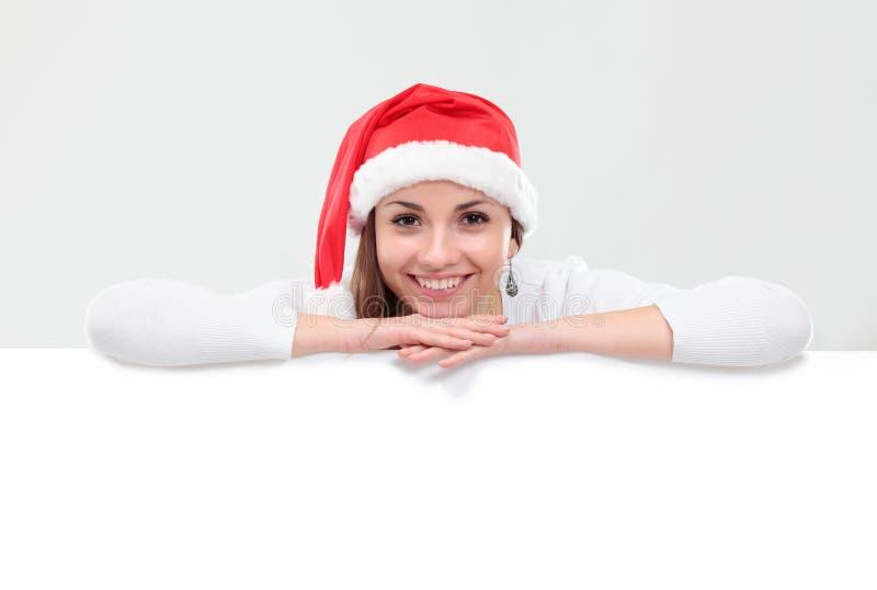 Mulher do Natal no chapéu de Santa que prende a placa vazia fotografia de stock royalty free