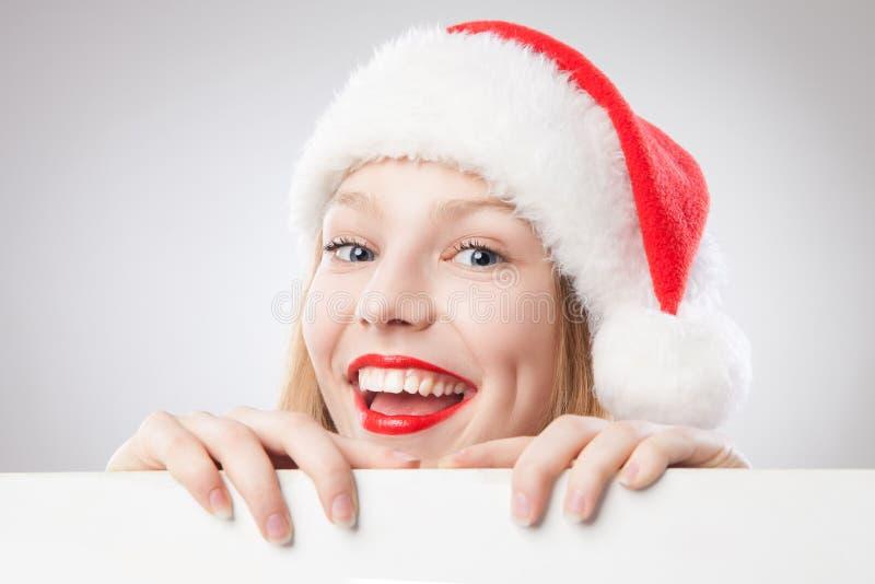 Mulher do Natal no chapéu de Santa que prende a placa vazia fotografia de stock