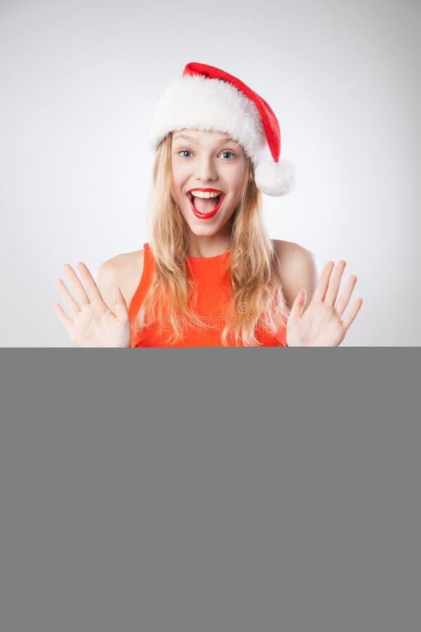 Mulher do Natal no chapéu de Santa que prende a placa vazia fotos de stock