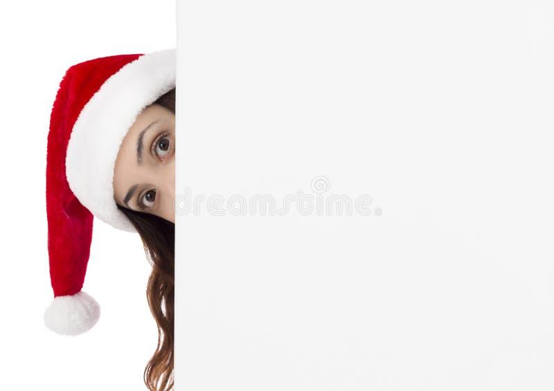 Mulher do Natal que olha curiosamente atrás de uma propaganda p imagem de stock