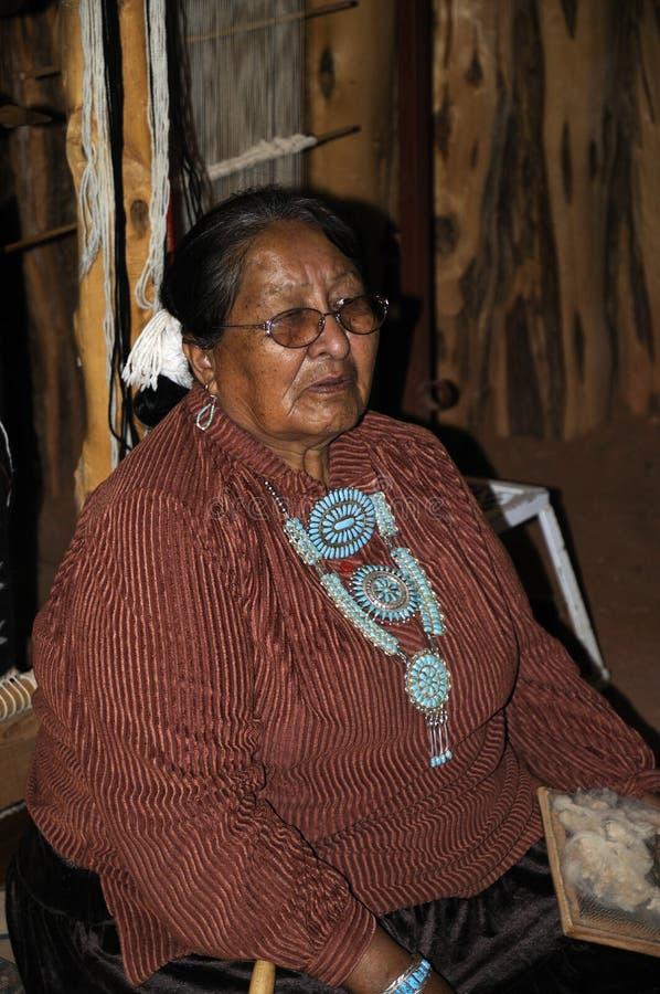 Mulher do Navaho em um hogan no vale EUA do monumento imagem de stock
