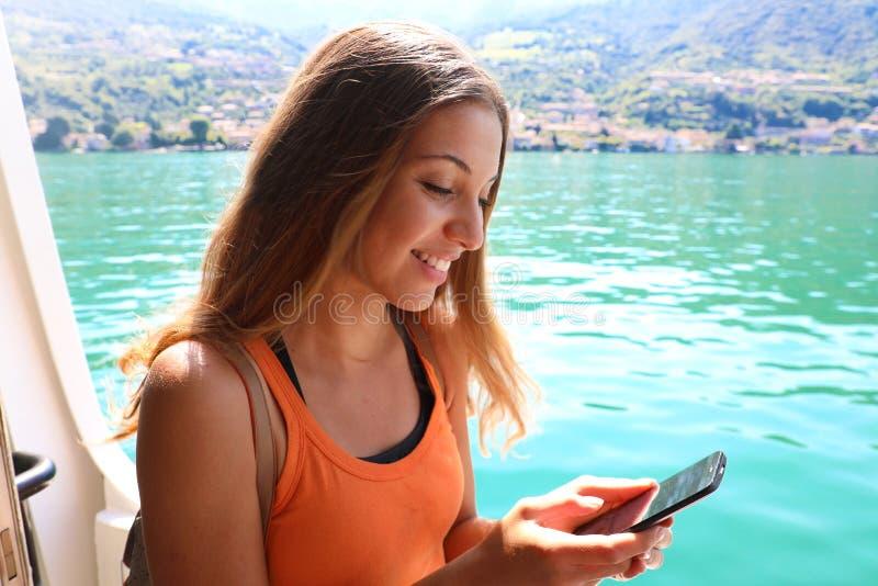 Mulher do navio de cruzeiros que usa o telefone celular em férias do curso Sms texting da menina ou utilização do Internet de Wif imagens de stock
