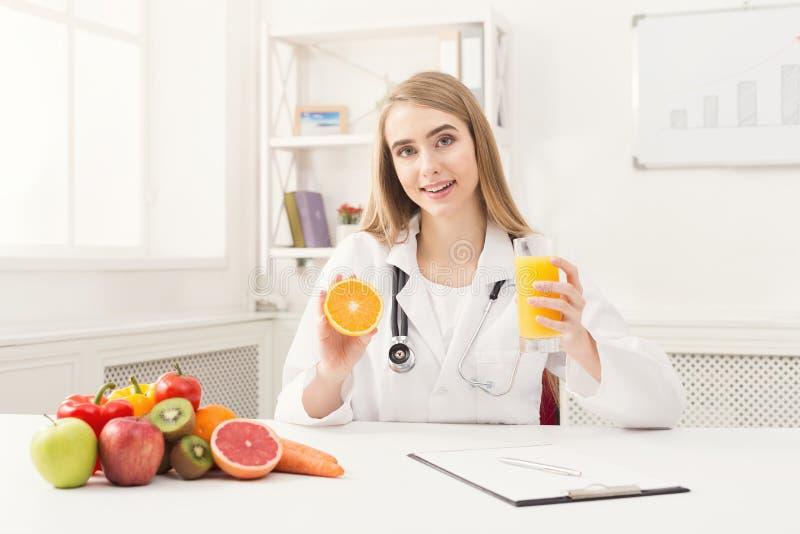 Mulher do nutricionista com fruto e suco fotos de stock royalty free