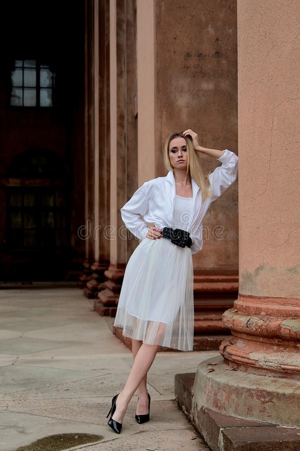 A mulher do olhar da forma Retrato moderno da jovem mulher Jovem mulher vestida na saia branca e na camisa que levantam perto da  fotos de stock royalty free