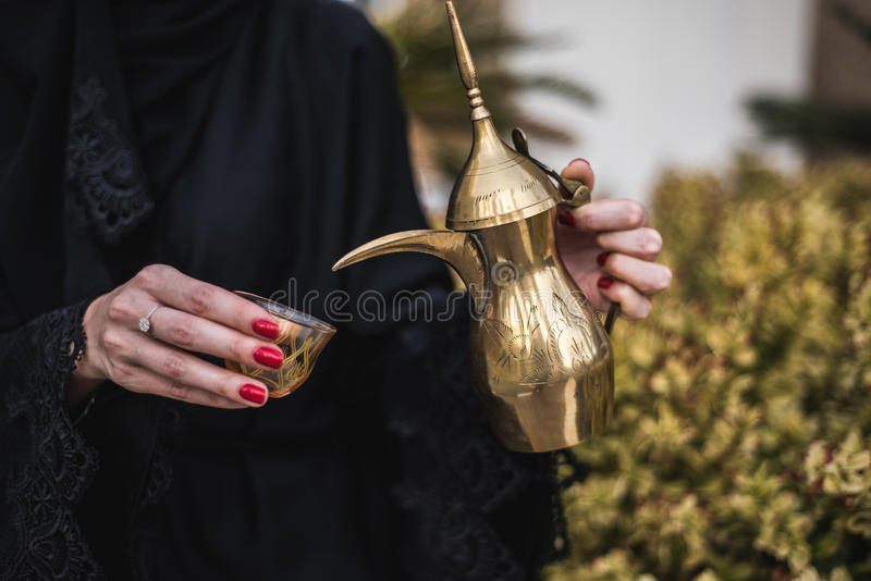 Mulher do Oriente Médio que oferece o café árabe imagens de stock