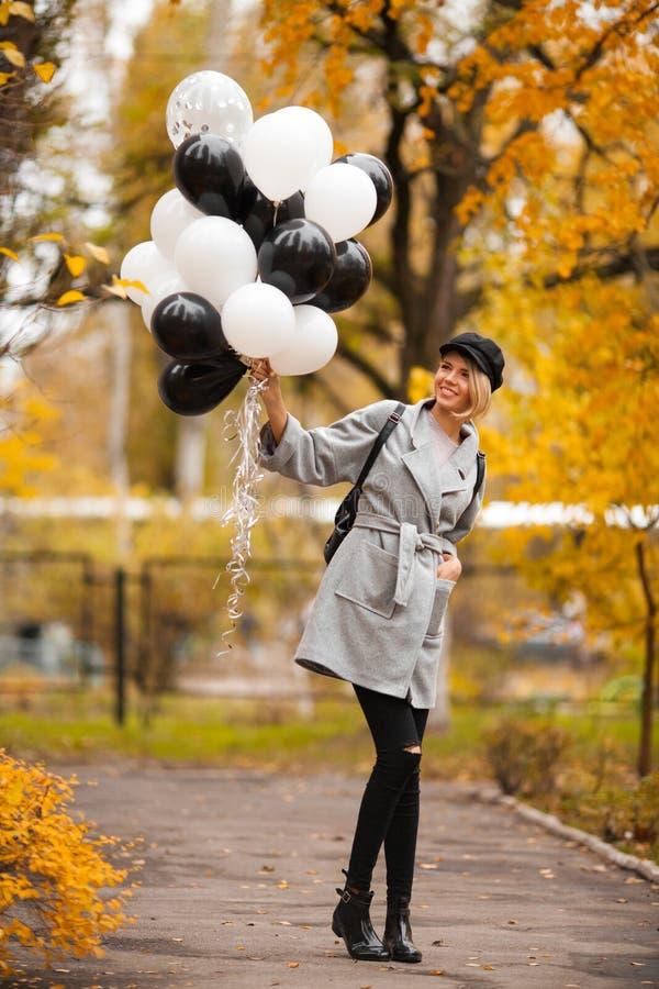 Mulher do outono no parque do outono com balões Menina da forma no revestimento cinzento foto de stock royalty free