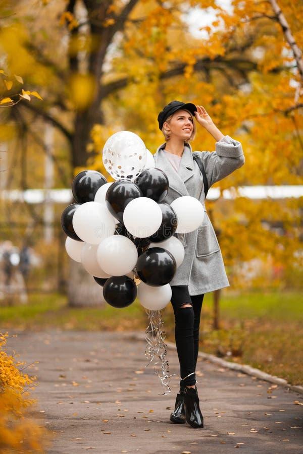 Mulher do outono no parque do outono com balões Menina da forma no revestimento cinzento fotografia de stock royalty free