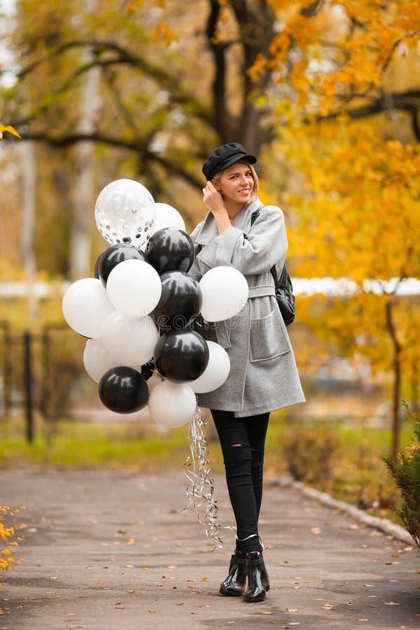Mulher do outono no parque do outono com balões Menina da forma no revestimento cinzento fotos de stock