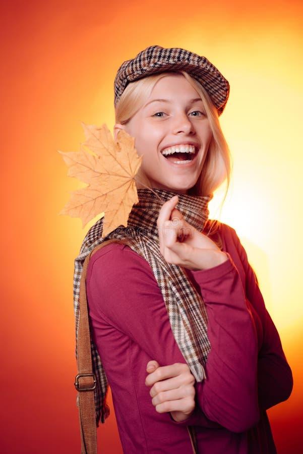 Mulher do outono que guarda a folha de ouro Jovem mulher atrativa que veste na roupa sazonal elegante que tem o humor outonal fotografia de stock royalty free