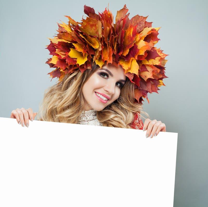 Mulher do outono que guarda o fundo vazio branco da placa de papel com espaço da cópia para anunciar o mercado ou a colocação do  foto de stock