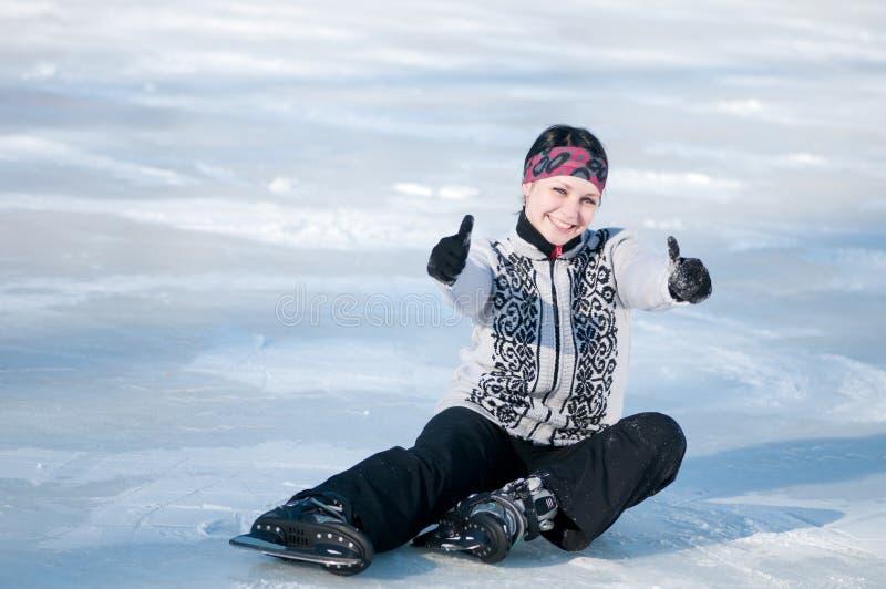 Mulher do patinagem no gelo que senta-se no gelo fotografia de stock