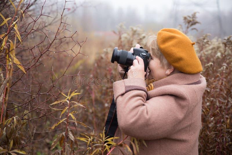 Mulher do pensionista com a câmera exterior imagem de stock