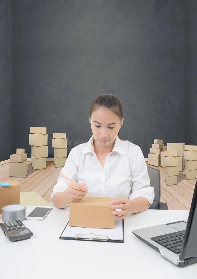A mulher do proprietário empresarial que trabalha a compra em linha prepara o processo de empacotamento do produto imagens de stock