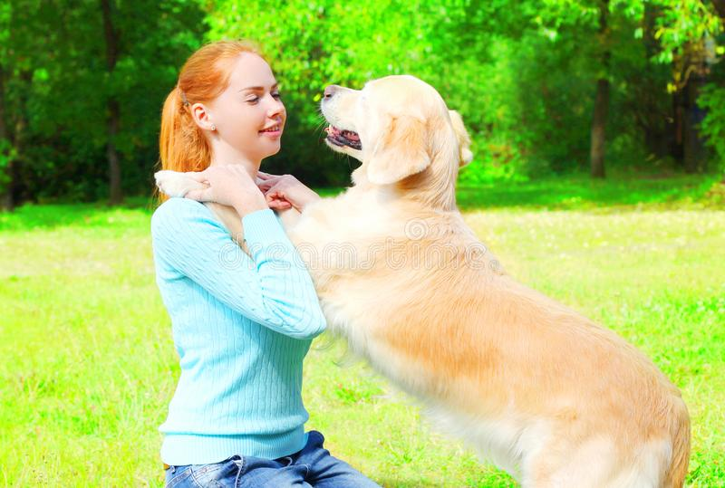 A mulher do proprietário está treinando seu cão do golden retriever na grama fotos de stock