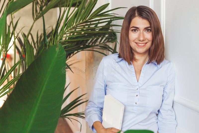 Mulher do psicólogo com o livro no escritório com plantas tropicais imagens de stock royalty free