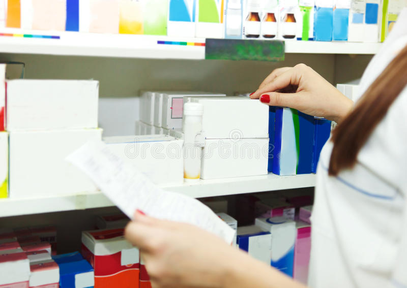 Mulher do químico do farmacêutico com prescrição em uma drograria imagens de stock royalty free