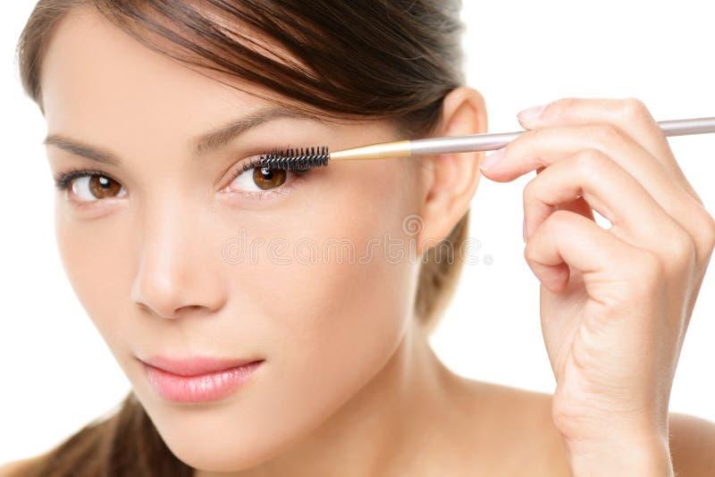 Mulher do rímel que põe a composição sobre o close up do olho imagem de stock royalty free