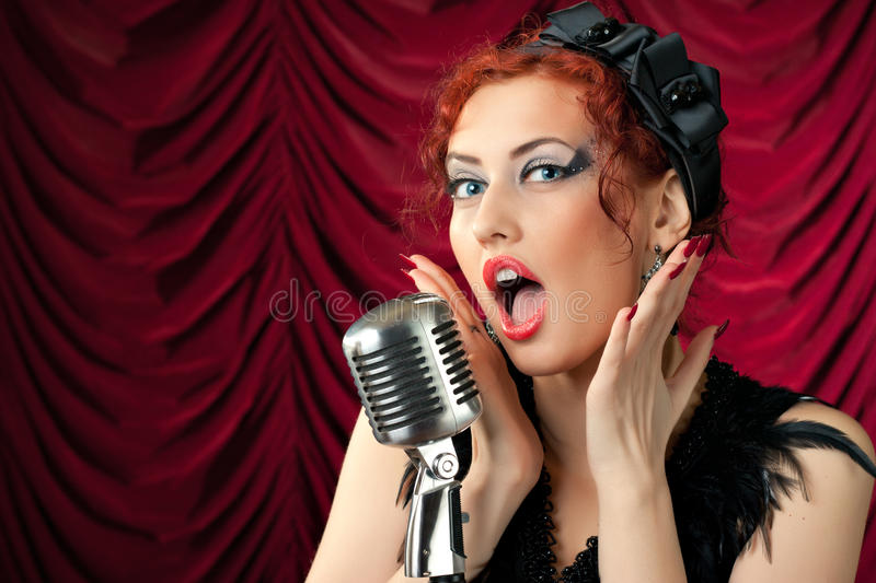 Mulher do Redhead que canta no microfone do vintage fotografia de stock royalty free