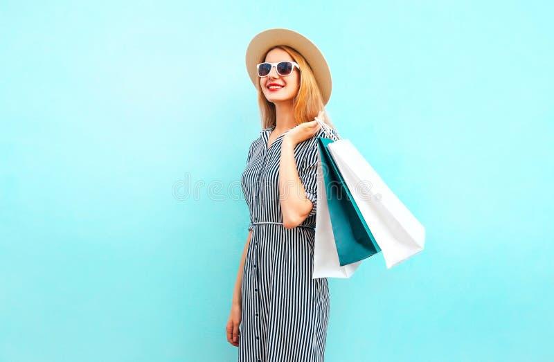 A mulher do retrato da forma anda com os sacos de compras em vestido listrado imagem de stock royalty free