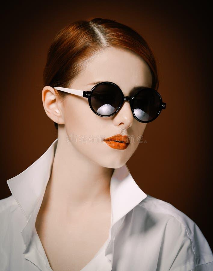 Mulher do ruivo do estilo na camisa e nos óculos de sol brancos fotos de stock royalty free