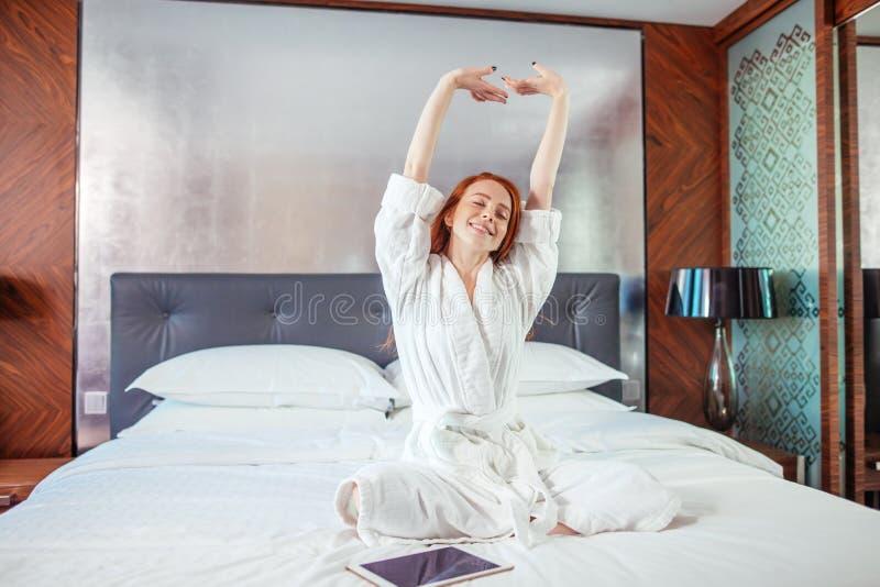 Mulher do ruivo que estica na cama após acordar imagem de stock