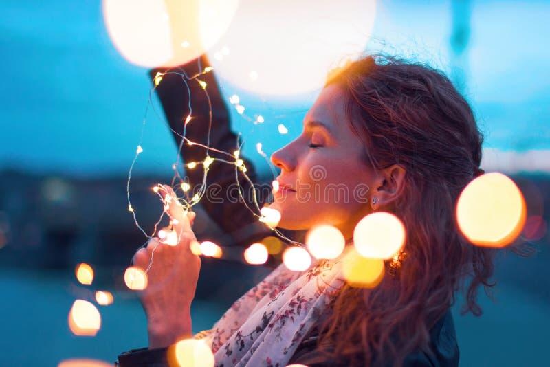Mulher do ruivo que guarda a festão da luz feericamente na noite e no dreamin fotografia de stock