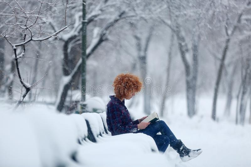 Mulher do ruivo que lê um livro na neve fotos de stock