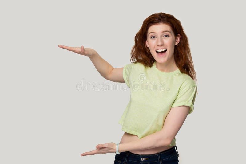 A mulher do ruivo que mostra algo alto com mãos sente feliz satisfeito imagens de stock