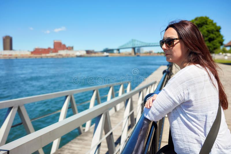 Mulher do ruivo que olha o cen?rio da cidade de Montreal e do Rio S?o Louren?o em um dia de ver?o ensolarado em Quebeque, Canad? foto de stock