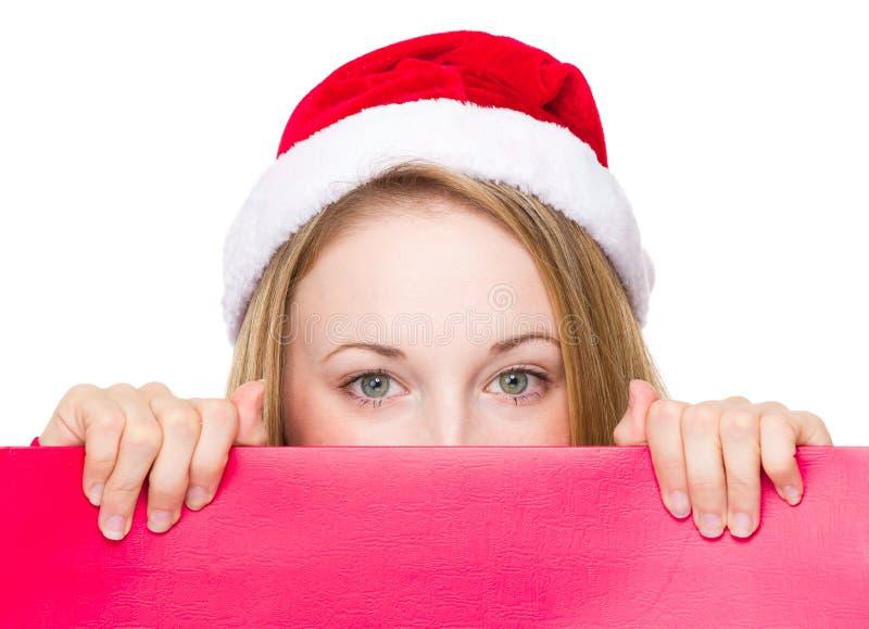 Mulher do sinal do Natal que espreita sobre a placa vermelha foto de stock