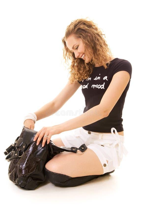 Mulher do smiley que procura algo em sua bolsa imagens de stock