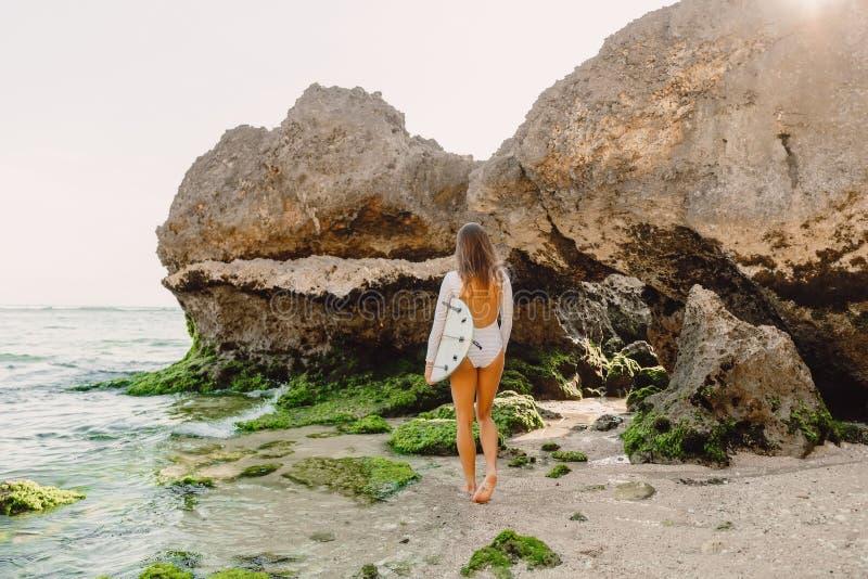 Mulher do surfista com prancha Surfar no oceano fotos de stock royalty free