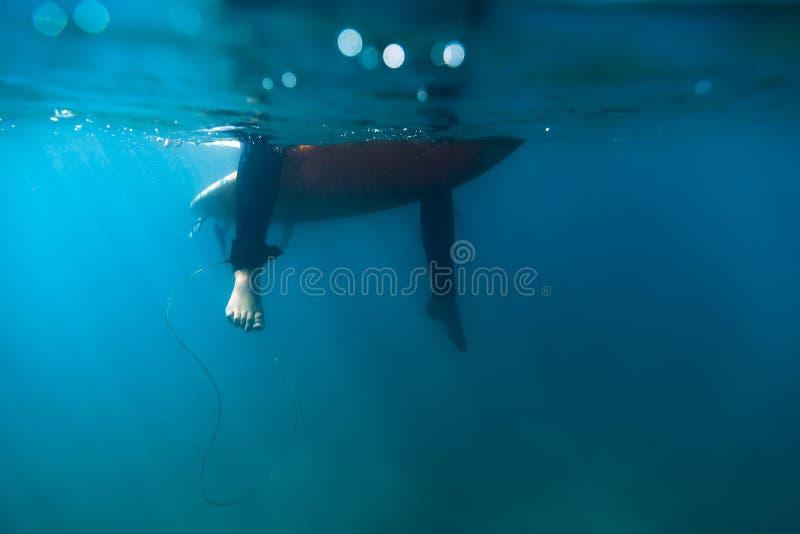A mulher do surfista está sentando-se na prancha no oceano Surfista e oceano foto de stock