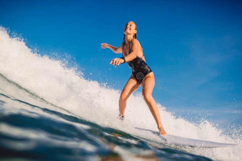 Mulher do surfista no passeio da prancha na onda de oceano Mulher no oceano durante surfar imagem de stock royalty free