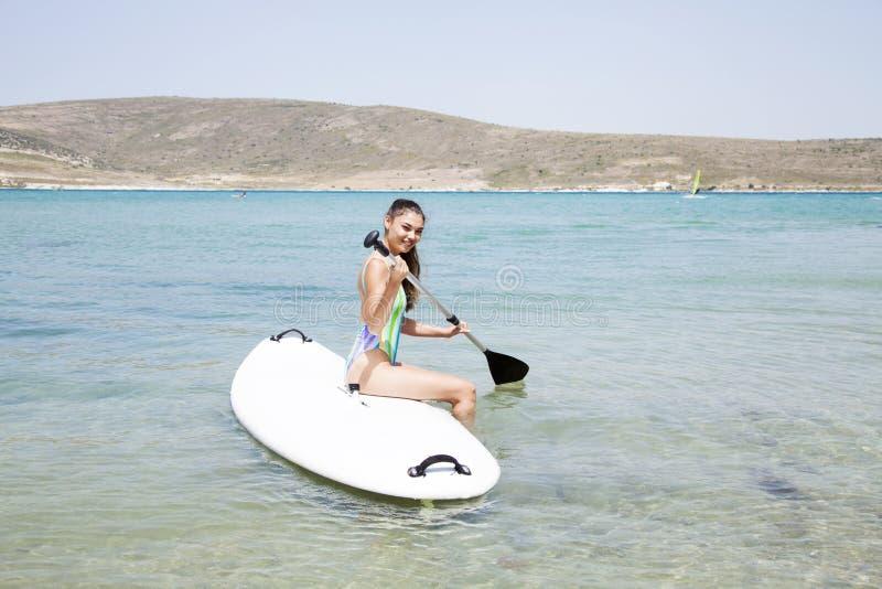 Mulher do surfista que surfa no oceano foto de stock