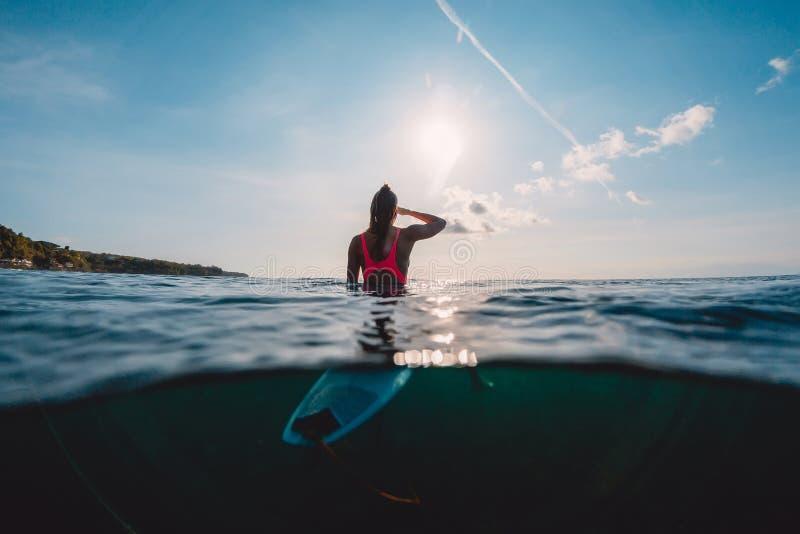 A mulher do surfista vê ondas com prancha Menina da ressaca no oceano fotos de stock royalty free