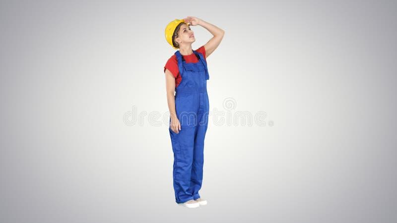 Mulher do trabalhador da construção do coordenador que olha acima em uma construção ou estatísticas ou gráfico que riem na extrem imagens de stock royalty free