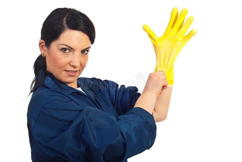 A mulher do trabalhador da limpeza põr a luva protetora fotografia de stock