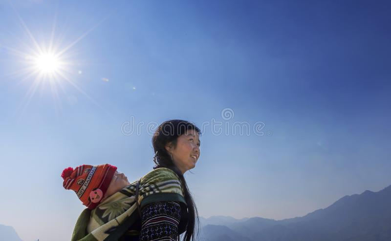 Mulher do tribo de Hmong que leva sua criança nela para trás em Sapa, Vietname fotos de stock