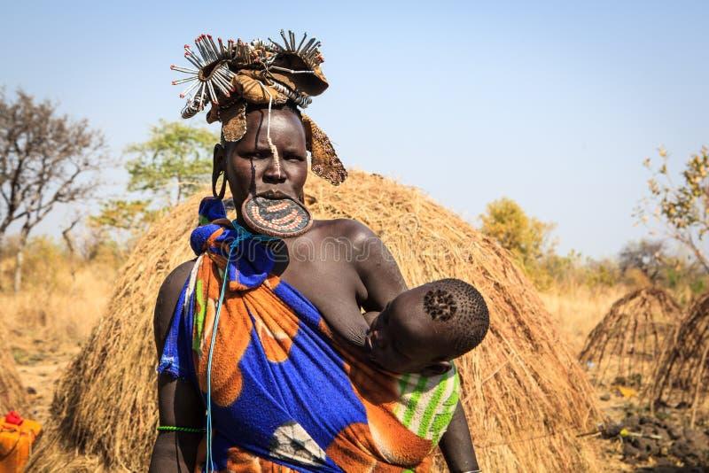 Mulher do tribo de Mursi que amamenta sua criança fotografia de stock royalty free